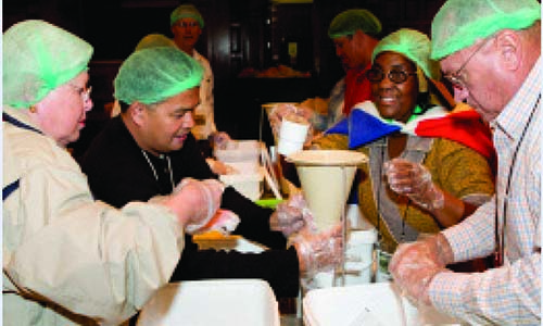 Conference participants pack 100,000 meals for children